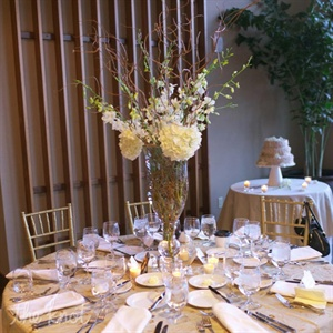 Tall glass vases were loosely filled with earthy arrangements of curly willow branches, white orchids and hydrangeas.