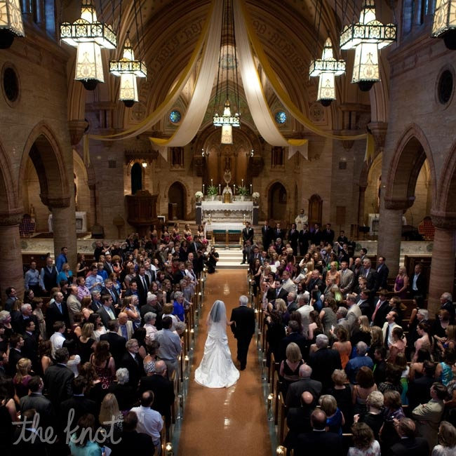Hurricane vases filled with lily grass and floating candles added an ethereal glow to the long church aisle.