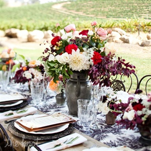 Overlooking the vineyards, the head table and the guest tables were long farm tables made of reclaimed wood. Vanessa of Alchemy Fine Events designed toile table runners with graduated linen ruffles on either end. Antique teapots, goblets, and country pitchers were filled with David Austin English garden roses, Black Magic roses, Queen Annes lace,  ...