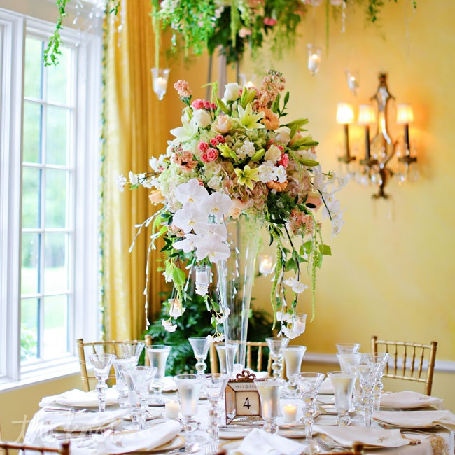 The high centerpieces contained hanging candles. Danae and Michael also incorporated a hanging flower arrangement element, which dangled from the chandeliers.