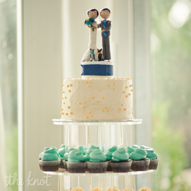A mini cake topped off three tiers of colorful cupcakes.