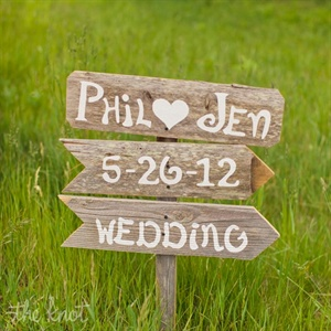 Painted wood signs welcomed guests at the ceremony entrance.