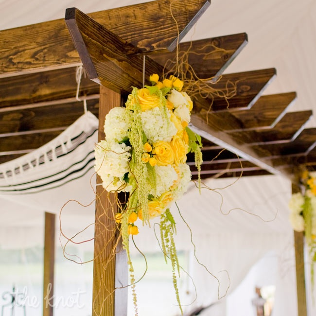 Yellow roses, green amaranthus and ivory hydrangeas hung from the wooden huppah.