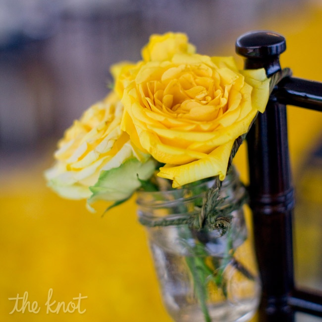 Mason jars filled with yellow roses hung from chairs at the ceremony.