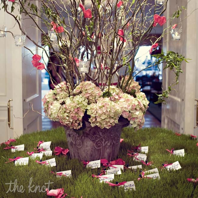 Tall branches dressed in pink petals and glass votives, and wrapped with hydrangeas served as a fresh focal point for the escort card table.