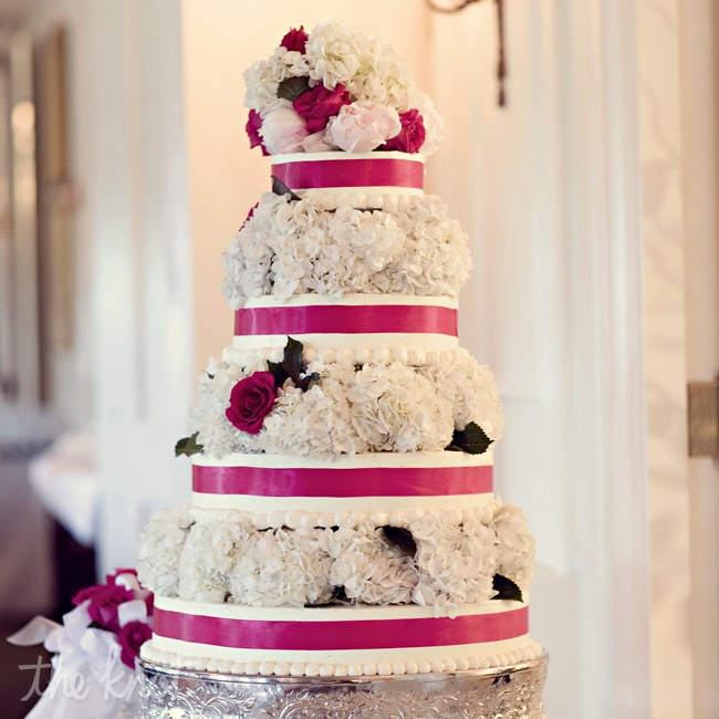 Fresh hydrangeas and roses separated each layer of the white-and-pink confection.