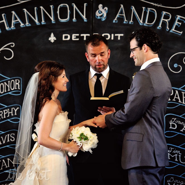 The couple exchanged vows in front of a chalkboard decorated with the names of their parents and members of the wedding party.