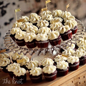 In lieu of cake, the couple served different flavors of cupcakes, many decorated with handmade gold flags.