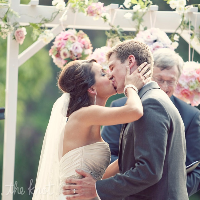 The couple exchanged vows in front of a white arbor decorated in ivy, white blooms and pink pomanders.