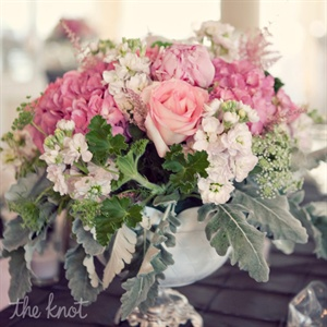 A variety of vintage containers and centerpiece styles-some tables with one large arrangement and others lined with smaller groups-added interest. Flowers in shades of pink with accents of geranium, leaves, dusty miller and Queen Anne's lace tied the look together.