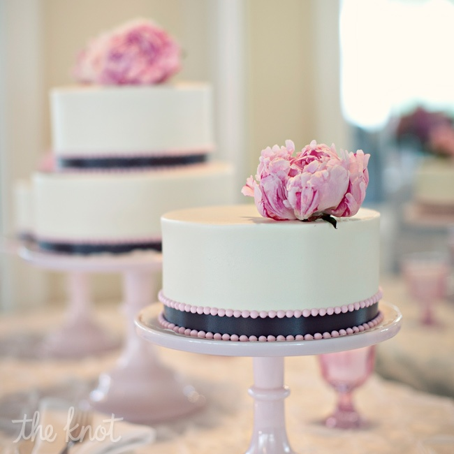 To give the dessert table a retro vibe, the couple topped it with a trio of smaller cakes on milk-glass stands. Each cake tier was wrapped in charcoal ribbon and pink pearl piping.