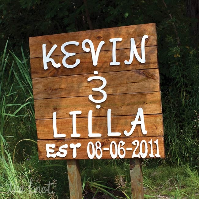 A wooden sign directed guests to the entrance of the wedding location.
