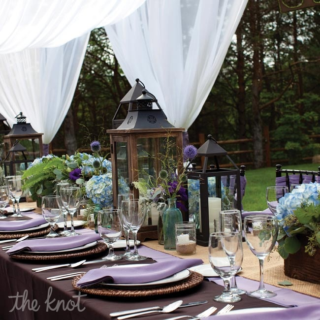 Lanterns and arrangements of purple and blue flowers and greenery lined tables. Lilac and plum linens created an elegant contrast.