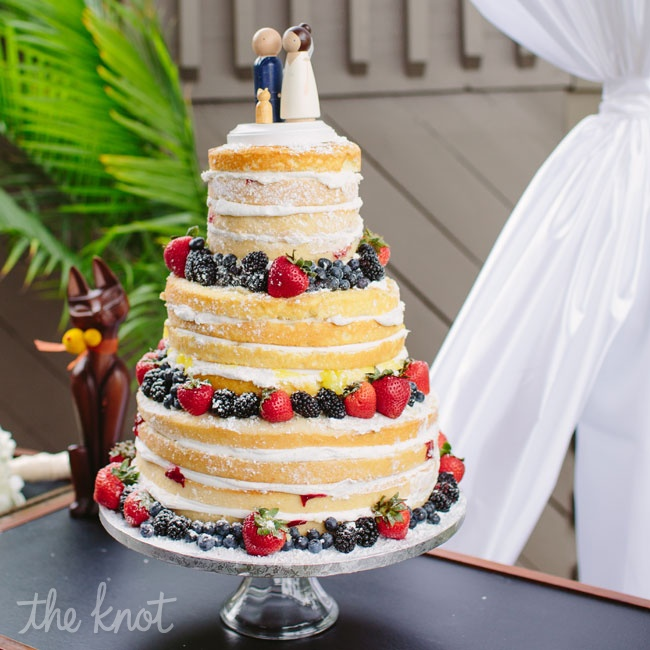 "Fresh fruit and wooden figurines topped the unfrosted wedding cake. Erica says, ""It was the most delicious cake we've ever tasted!"""