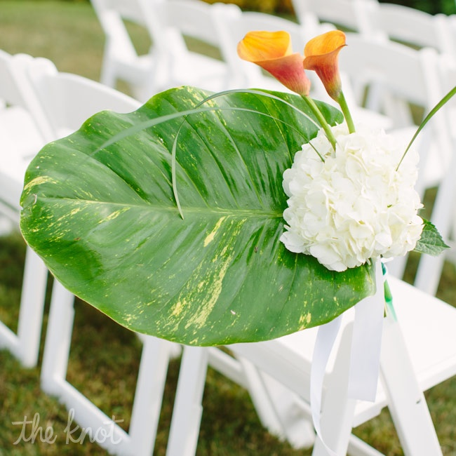 Because their ceremony surroundings were so beautiful, the couple only added decorations to the chairs in the way of a large leaf, white hydrangeas and an orange calla lily blossom.