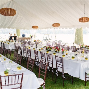 The airy white tent was decorated with crisp white linens, wooden chiavari chairs and hanging brown lanterns.