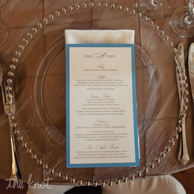 Blue and white menu cards detailing the wedding's four-course meal rested on top of glass and gold beaded chargers.