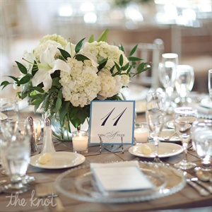 White hydrangeas, lilies and peonies topped the reception tables along with classic blue and white table numbers.