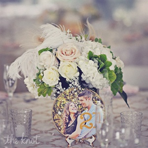 Glass votives and Mason jars were filled with soft hues of garden roses, baby's breath, feathers and greens. Jessica made the embroidered hoop table numbers using the couple's engagement photos.