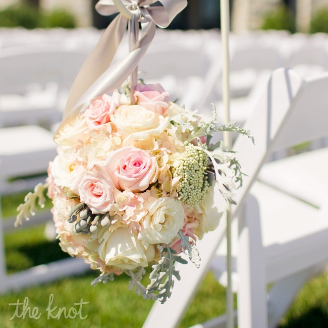 Pomanders made of pink roses, rice flowers, silver brunia and hydrangeas hung from shepherds hooks at the ceremony.