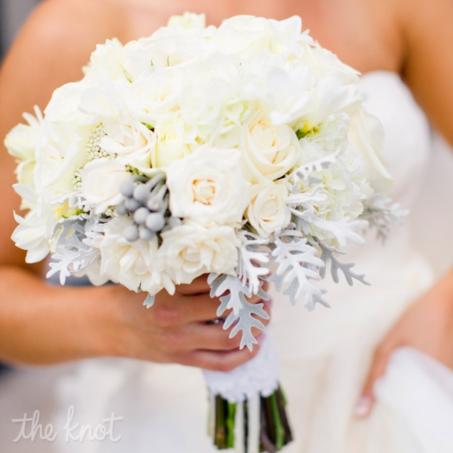 Kaitlin's textured bouquet contained a mixture of all-white roses, peonies, hydrangeas, freesia and rice flower. Pops of silver brunia and dusty miller complemented the look.