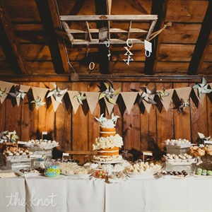 The couple's unfrosted wedding cake was the center of attention on their dessert table. Mini flags and pinwheels decorated the area to give the display a rustic yet playful vibe.