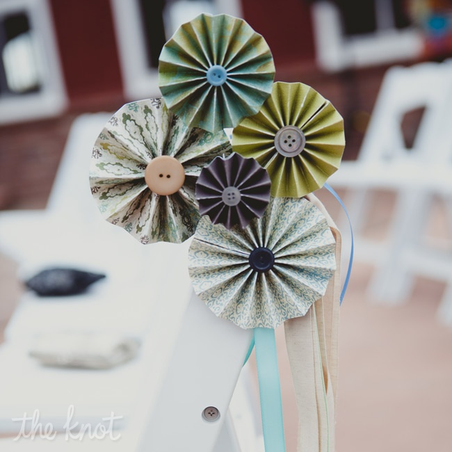 Handmade groupings of paper pinwheels and buttons formed flower-like arrangements on the ceremony chairs.