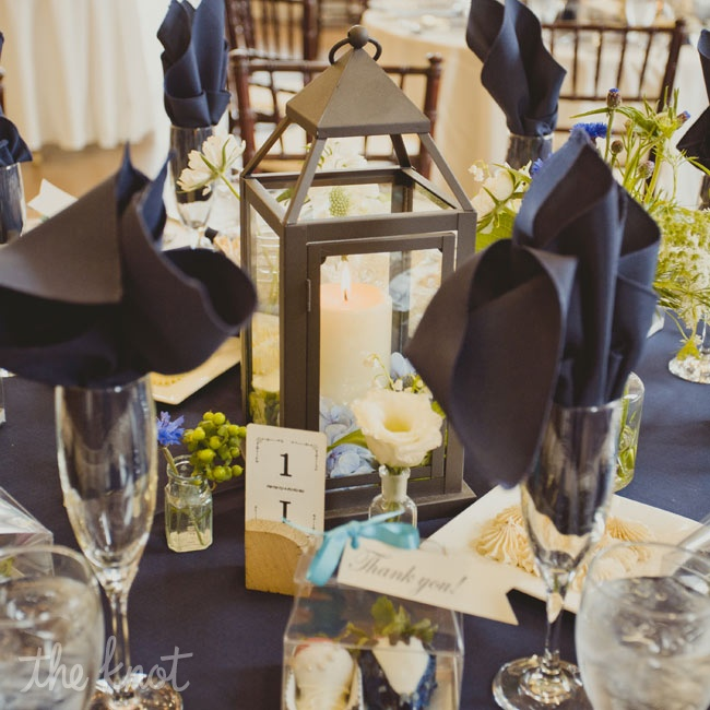 Rustic lanterns paired with small vases of white flowers topped reception tables along with champagne flutes stuffed with elegant blue napkins.