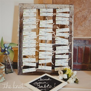 The couple's blue and green escort cards were clothespinned to wire fencing set in an old window frame.