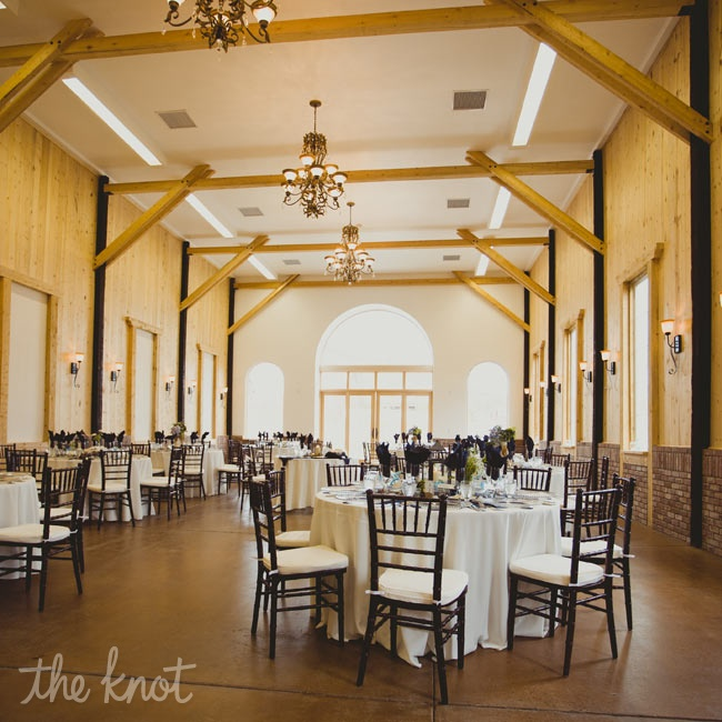 Crisp white linens and low centerpiece arrangements topped tables so as not to take away from the already striking rustic wooden panelling.