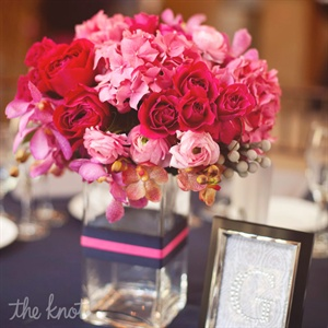 Pink roses, hydrangeas and orchids filled glass vases at the reception.
