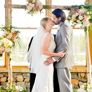 The couple exchanged vows in a reclaimed barn surrounded by birch branches adorned with bursts of roses.