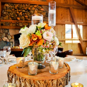 Vases filled with roses and orchids topped tree stump stands. Mercury glass votives and tall vases with floating candles added to the tablescapes.