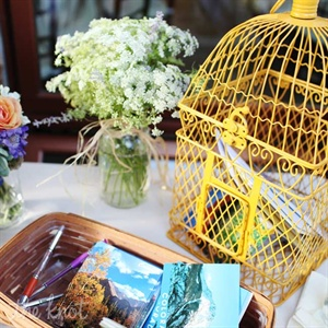 Guests wrote their well-wishes and advice to the newlyweds on vintage Colorado postcards and placed them in a yellow birdcage. Heather Dwight, the couple's planner mailed them to the couple every few weeks following the wedding.