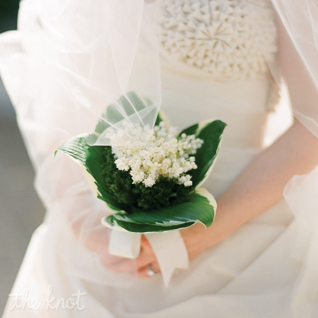 This wintry bridal bouquet was a nosegay of lily-of-the-valley and green moss finished with ribbon.