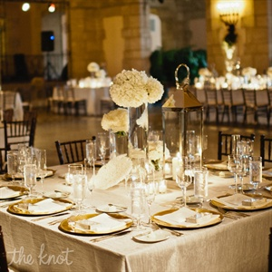 Modern elements, like white hydrangeas in glass cylinders and sleek stemware, mixed with traditional flatware and gold chargers. White coral and silver lanterns incorporated a subtle nod to the beach.