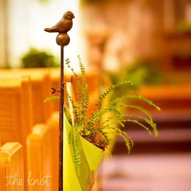 Bronzed bird stands lined the ceremony aisle holding cones filled with fresh green ferns.