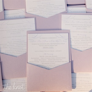 Metallic-lilac pockets held programs printed on ivory paper.