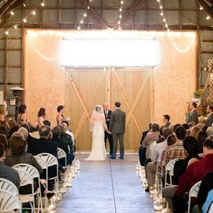 The couple&#39;s ceremony was held indoors. The aisle was lined with votives and string lights hung from the ceiling for a romantic effect.