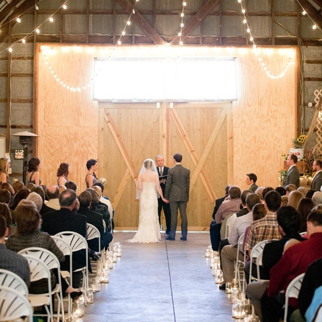 The couple's ceremony was held indoors. The aisle was lined with votives and string lights hung from the ceiling for a romantic effect.