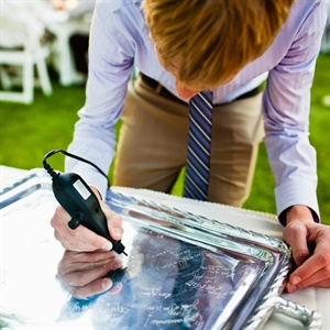 In lieu of a guest book, Kelley and Matt had their guests sign a pewter tray with an etching tool. Kelley noted that the etching was very loud, so it's she wouldn't recommend it for an indoor wedding. Now, Kelley and Matt use the tray as a personalized centerpiece.