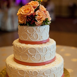The couple's ivory fondant cake was decorated with scrolling designs and coral ribbon around each tier. Peach roses served as a bright topper.