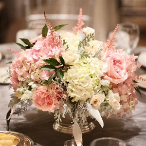 Pink and white roses, astilbe, stock and hydrangeas were displayed in low silver urns at the reception.