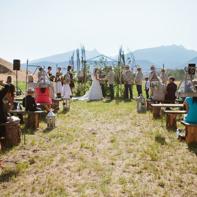 The ceremony was held outside facing the mountains including Trapper Peak. The ceremony began just after 4pm. The guests'  benches were hammered together by the men in the wedding from stumps and wooden slabs. The aisle was decorated with old lanterns filled with florals, weathered tin pillars, aspen bark cylinders, and old wagon wheels.