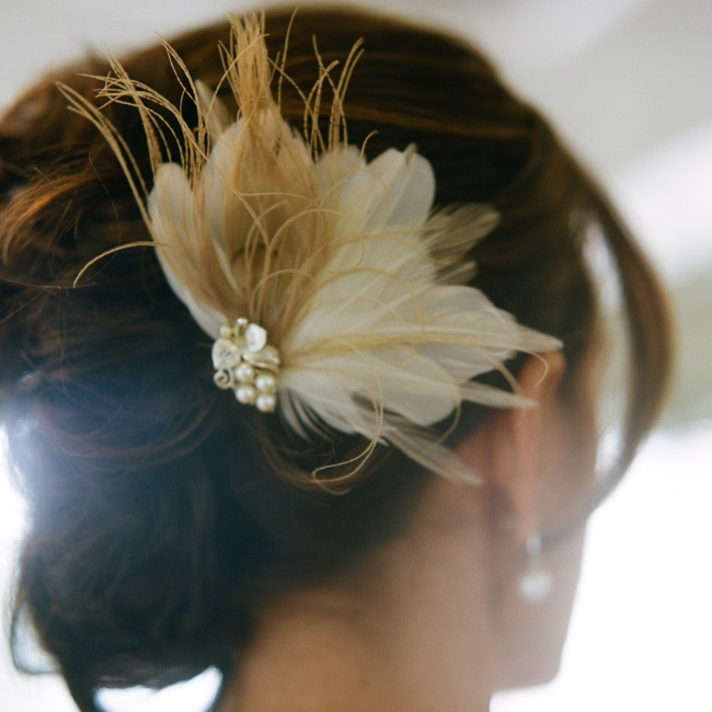 Paige wore a delicate feather fascinator pinned into her romantic updo.