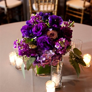 Bold, vibrant arrangements of purple flowers like roses and stock topped the reception tables. Small votives added a touch of romance to the tablescape.