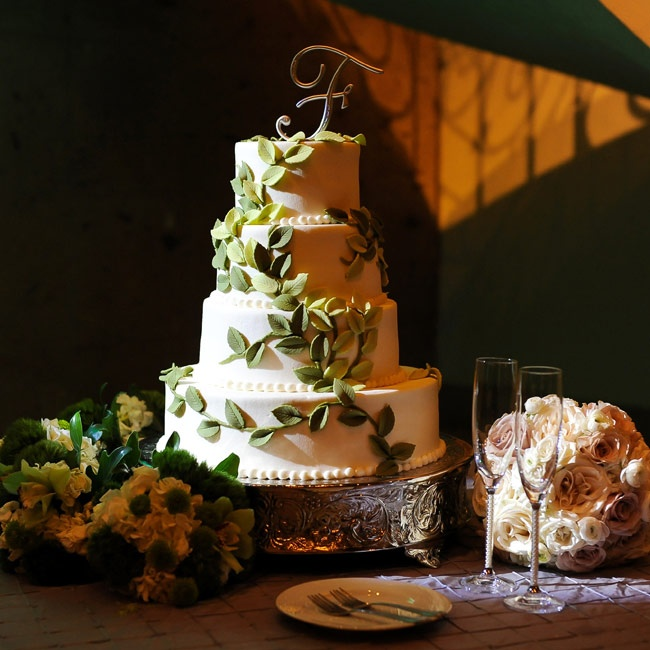 As a nod to their wedding invitation design and the couple's eco-chic theme, green fondant leaves decorated the four-tiered cake.