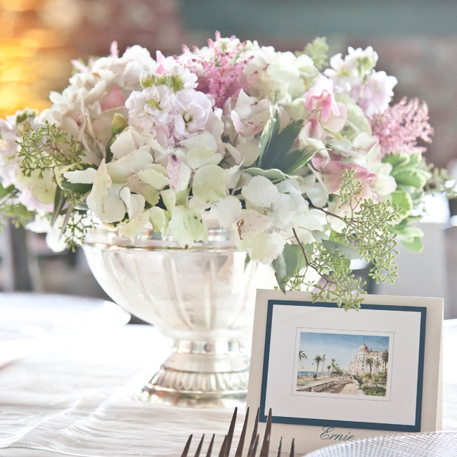 Pink hydrangeas, light pink stock, sahara roses and like pink sweet peas filled silver urn vases. Each guests' place card was a picture of a notable places to visit in Paris.