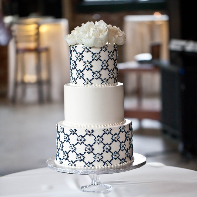 Heidi designed the wedding cake to match the couple's stationery. A geometric navy design covered two of the tiers, while fresh white peonies finished the look on top.