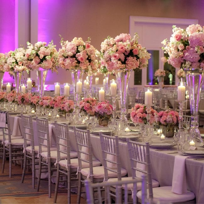 The reception head table had a mixture of high and low glass centerpieces of pink hydrangeas, roses and orchids. Pillar candles add romance to the scene.
